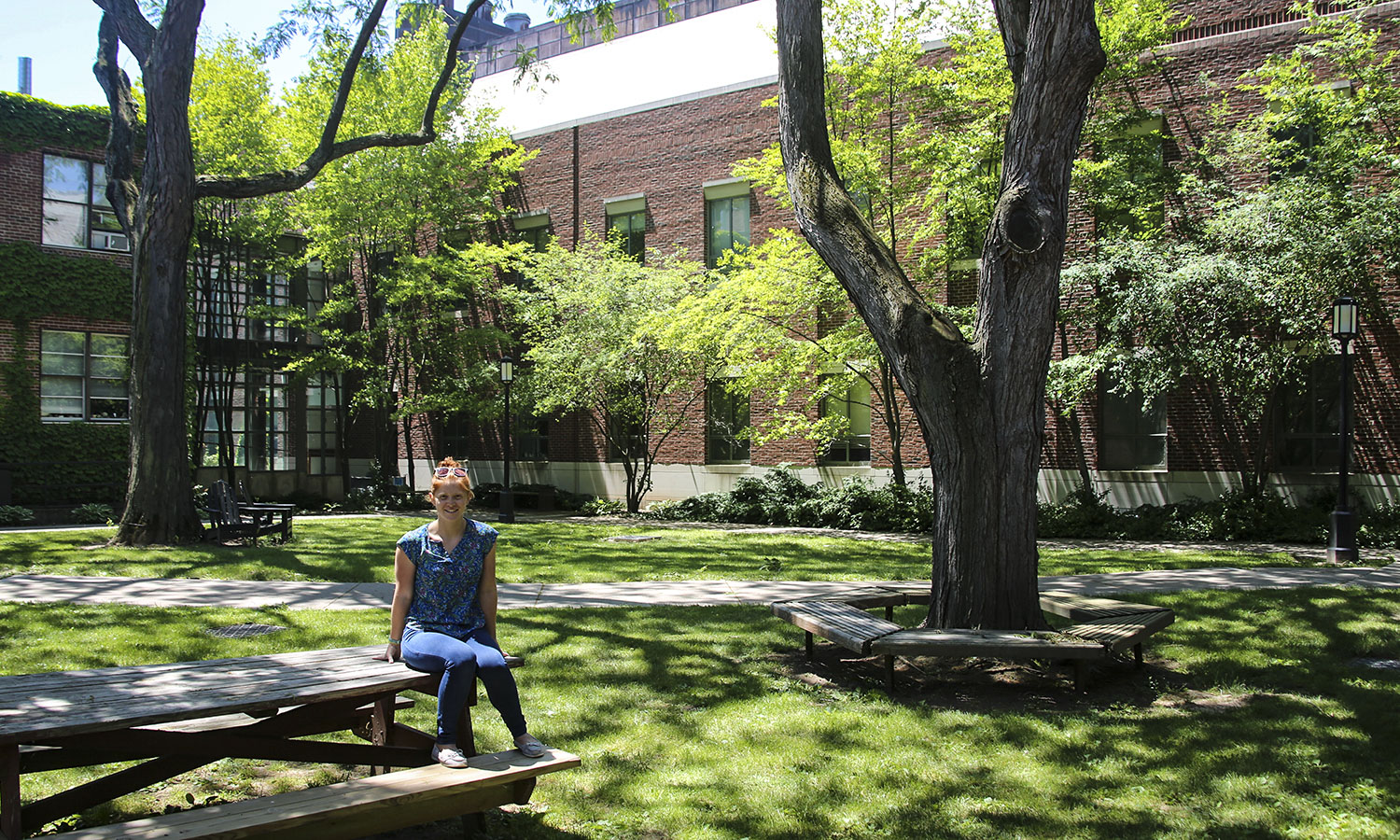 "Therese Mandracchia '19, a Biochemisty major, sits in the small quad in the middle of the sciences complex. This is her favorite place on campus because in the summer, ""it's shady and breezy."" Therese is continuing her studies as a graduate student at Penn State University."