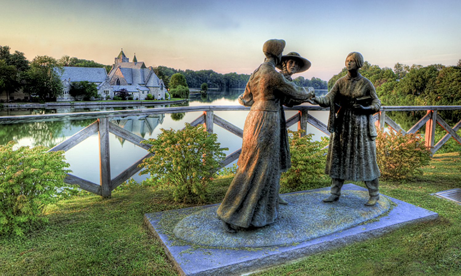 In Seneca Falls, the home of the women's rights and suffrage movements, a statue of Elizabeth Cady Stanton, Susan B. Anthony and Amelia Bloomer created by Professor of Art Ted Aub commemorates the meeting of the influential women. Trinity Church stands in the background.