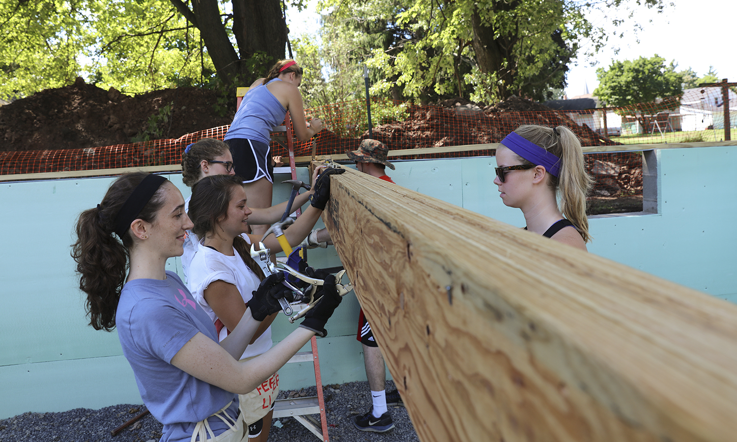 Students help the Geneva Boys and Girls Club construct a new play area during a Day of Service, one of several hosted throughout the year. The 25-year tradition is one of the most popular on campus.