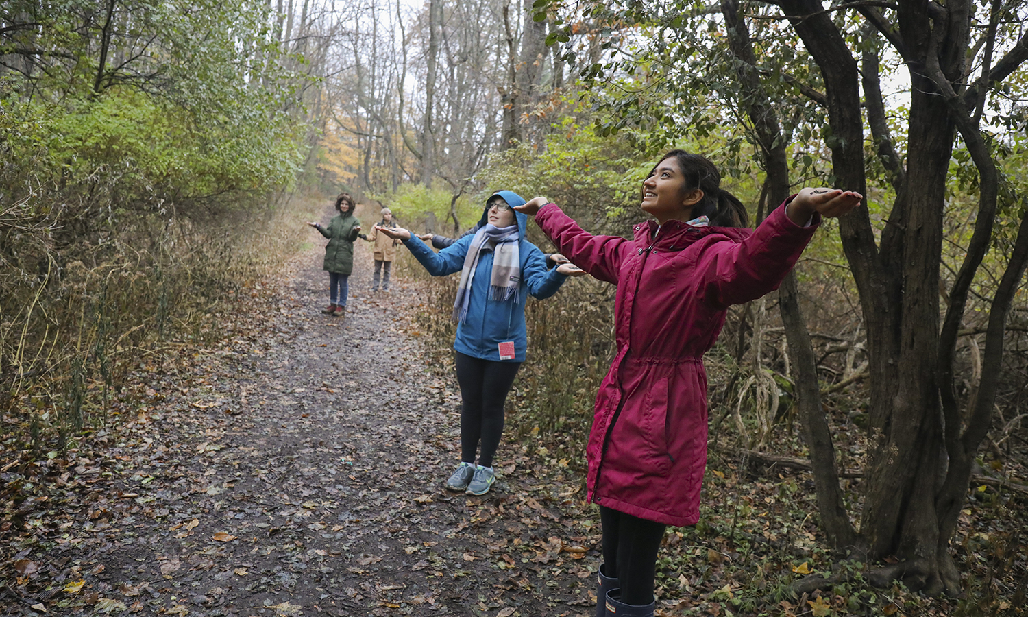 "Natalie Booth '18 and Shweta Patel '18 hold handfuls of birdseed to attract wildlife at Montezuma National Wildlife Refuge as part of the course ""Ornithology"" with Professor of Biology Mark Deutschlander."