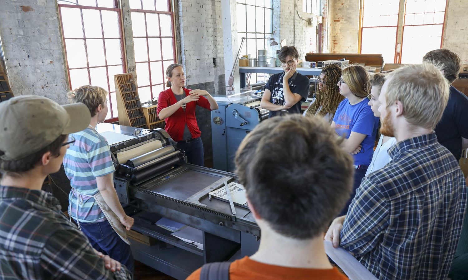 Associate Professor of English and Comparative Literature Kathryn Cowles speaks to students about the printing press during a visit to the Cracker Factory in Geneva, N.Y.