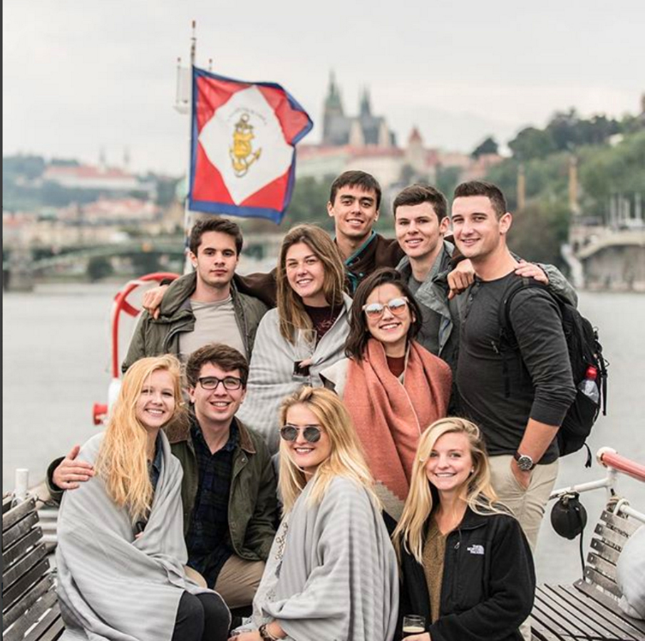 Students studying abroad in Prague pose for a photo during a boat cruise on the Vltava River.