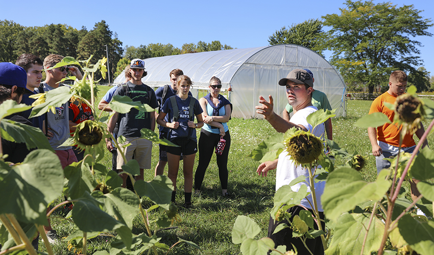 Teaching colleague Ben Gamache explains the purpose of the existing garden as students prepare to expanded the existing vegetable garden for new garlic beds.