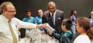 As part of a visit to the Boys and Girls Club, President Gregory J. Vincent '83 helps Executive Director Chris Lavin '81 (left) hand out HWS water bottles to students in the Summer University program.