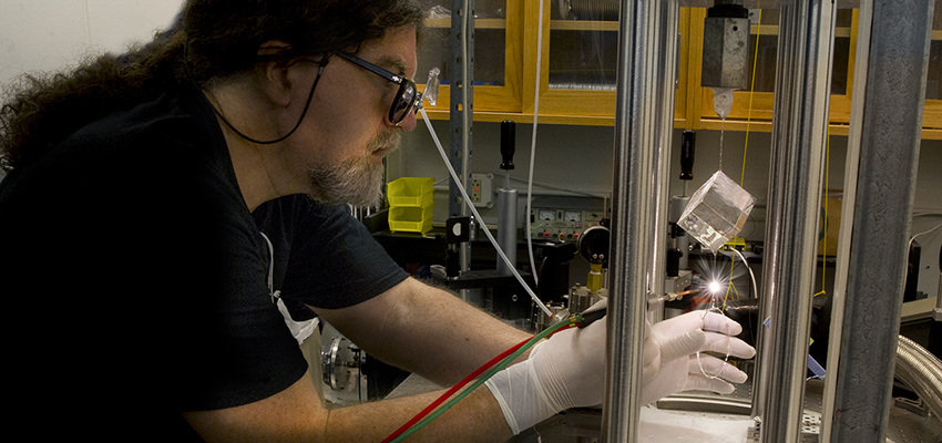 Associate Professor of Physics Steven Penn welds the suspension of a LIGO coating sample. The sample has a conductive coating, developed at Stanford, which allows stray charges on LIGO mirrors to be neutralized.