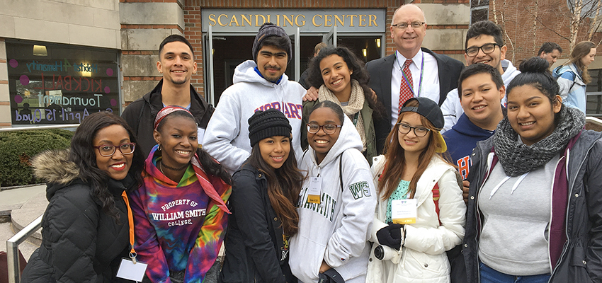 Assistant Director of Admissions Rose Cherubin and Director of Campus Safety Marty Corbett gather for a photo with members of HWS Posse 5 on the steps of Scandling Campus Center during HWS Scholar Day.
