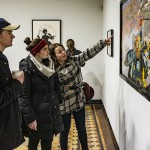 """At the Davis Gallery at Houghton House, students observe artwork on display from the collection """"Art and Labor: Works from the Art Collection."""" The exhibit will be on display through March 1st."""