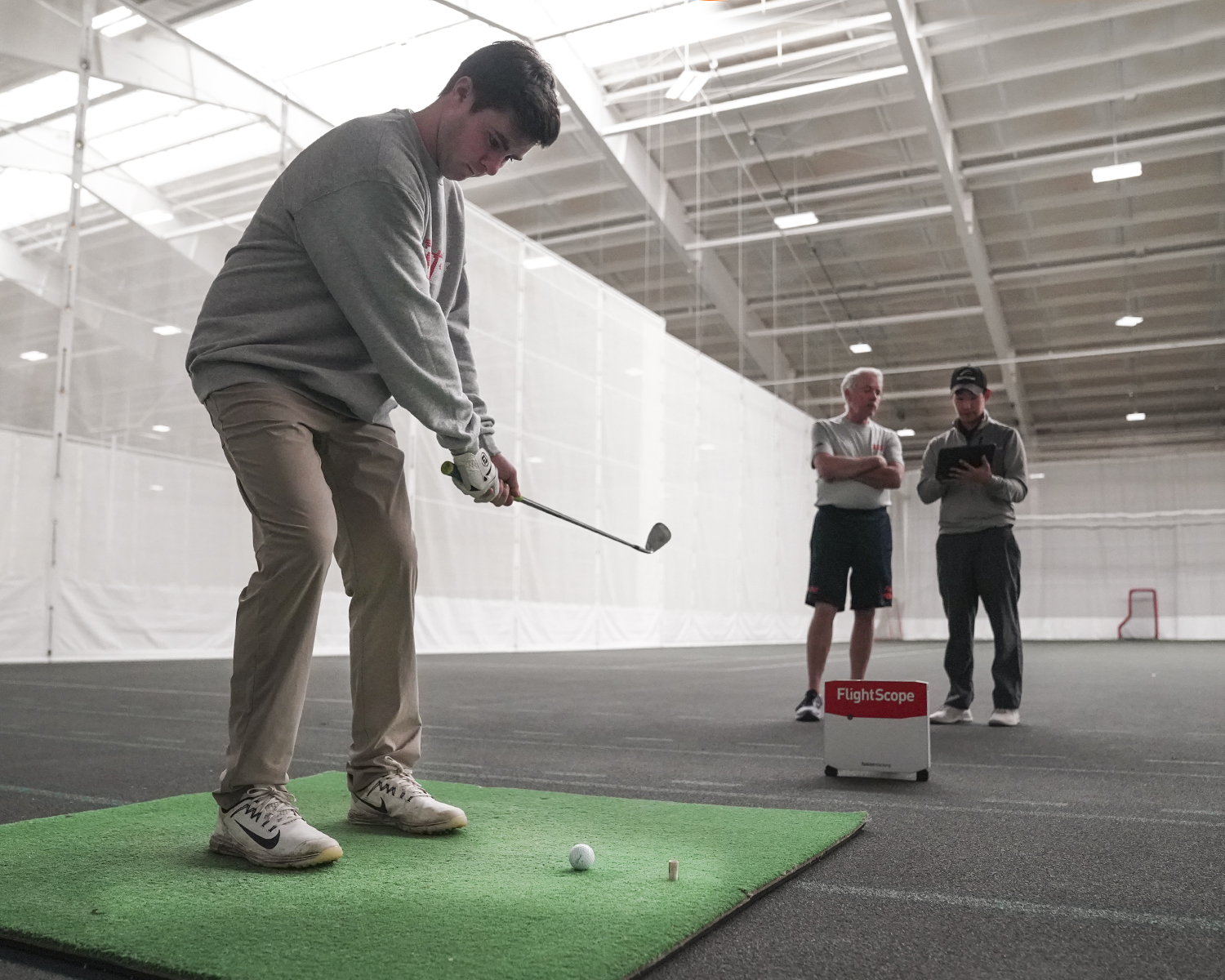 Zachary McCloskey '20 takes swings while Hobart Golf Head Coach Ken Dougherty learns how to use the new golf swing monitor from a  FlightScope representative.