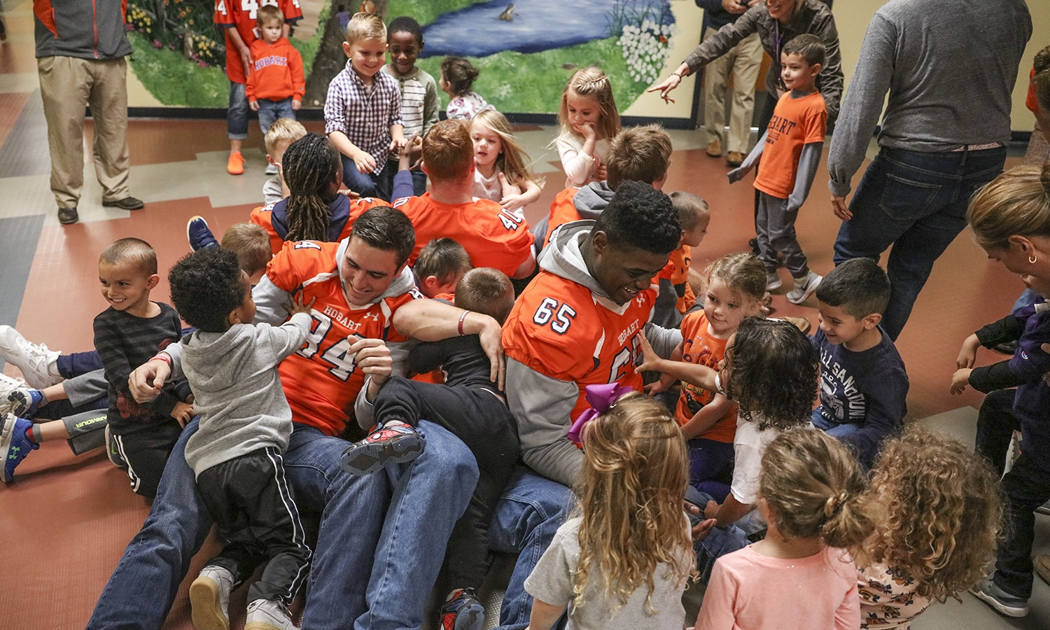 "As part of their third annual fundraiser ""Tackles and Touchdowns,"" Hobart Football visits the organization Happiness House to spend time with children enrolled in the program."