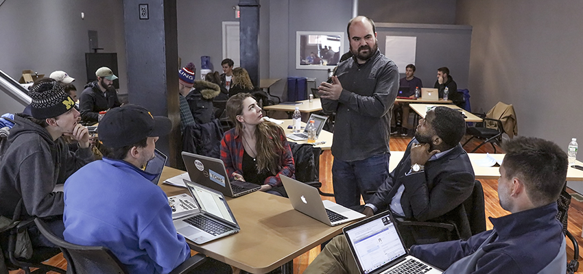 In the Bozzuto Center for Entrepreneurship, Visiting Assistant Professor of Entrepreneurial Studies Craig Talmage works with students on a marketing proposal as part of their senior capstone project.