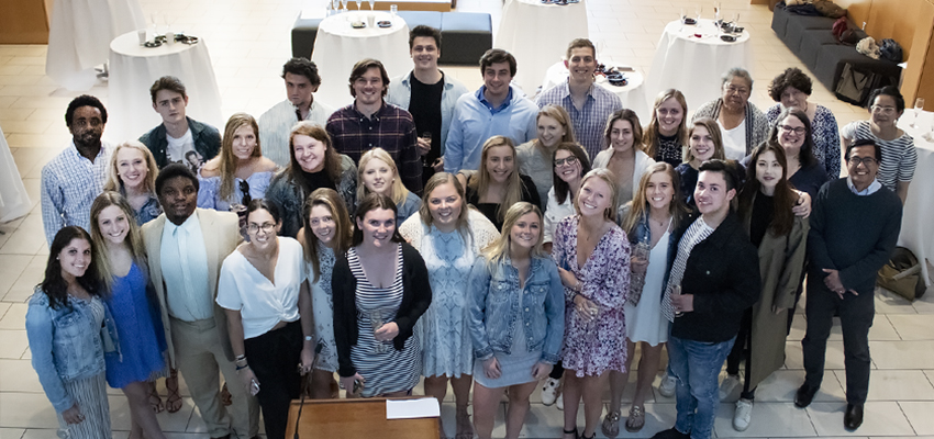 In the photo above, the 2019 media and society majors celebrate the accomplishments of their peers with members of the faculty in the Gearan Center for the Performing Arts.