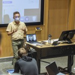 """Visiting Assistant Professor of Media and Society lectures during """"Introduction to Media and Society."""" Students learning remotely are projected into the classroom."""
