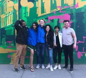 Wilson (right) and friends pose for a photo in front of a mural in downtown Geneva.